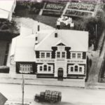1958; Aerial view English Scottish and Australian Bank. Has truck laden with apple crates driving past.